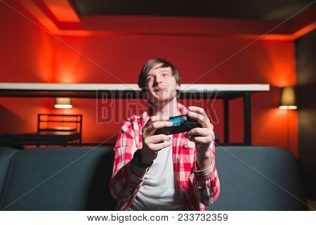 Gamer Sits On A Sofa With A Gamepad In His Hands And Plays Games On The Console. Gamer Concept Focus