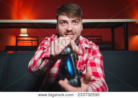 An Expressive Gamer Plays Video Games On The Console. An Angry Man With A Gamepad In His Hands Plays