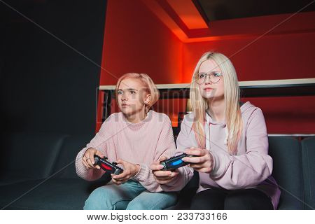 Girlfriends Compete In Video Games On The Console. Concentrated Girls With Joysticks In Their Hands