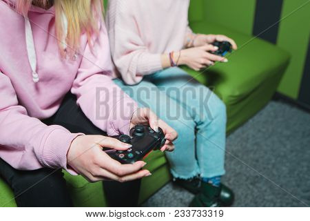 Female Hands With Gamepads While Playing On The Console Top View. Girls In Pink Dresses Play Video G
