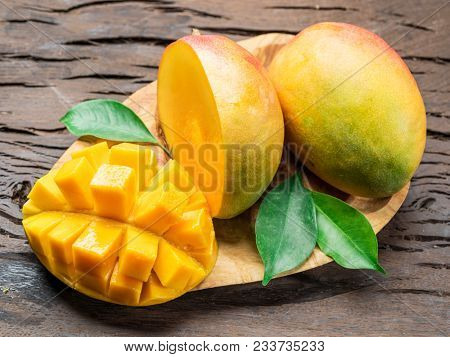 Mango fruits and mango slices on the old wooden table. Organic food.