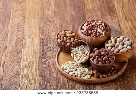 Mixed Nuts In Brown Bowls On Wooden Tray Over Rustic Background, Close-up, Top View, Selective Focus