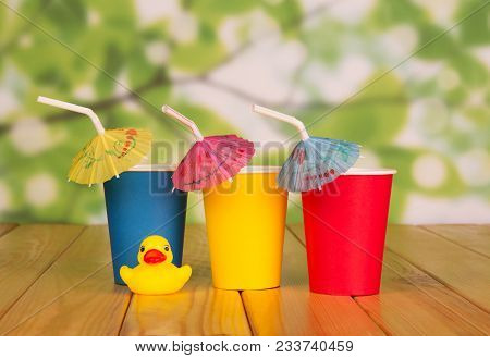 Three Colored Disposable Cups, With Straw And Umbrella Next To The Children's Toy On Light Green Bac