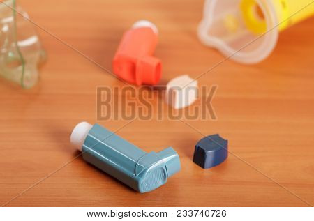 Small Portable Inhaler For Adults And Children, On Background Of Wooden Table
