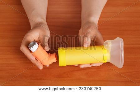 Female Hands Preparing Inhaler To Work, On Background Of Wooden Table