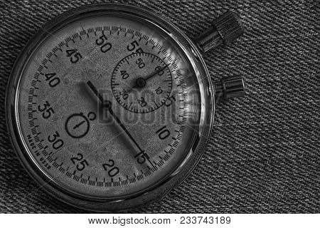Stopwatch, on worn denim background, value measure time, old clock arrow minute and second accuracy timer record. poster