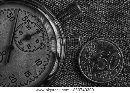 Euro Coin With A Denomination Of Fifity Euro Cents And Stopwatch On Worn Jeans Backdrop - Business B