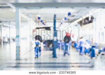 Blurred Background : Car Technician Repairing The Car In The Shop, Garage Or Service Station.