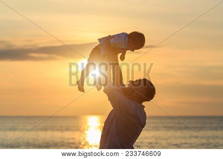Family On The Beach Concept, Caucasian Father Playing And Carrying His Son On The Tropical Beach In