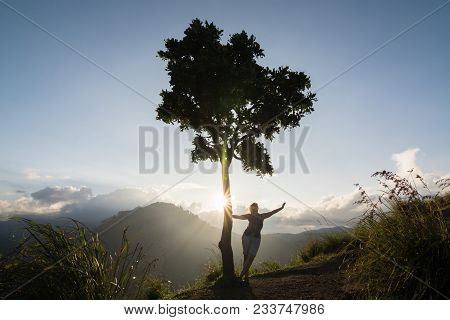 Backlight Silhouette Of A Woman And Tree On The Hill