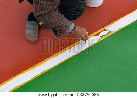 Worker Painting The Sideline On The Floor For An Outdoor Stadium