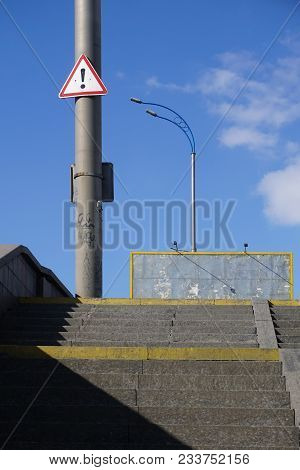 Road Sign, Black Exclamation Point In Red Triangle Hang On Pole, Warning About Danger. Light, Shadow