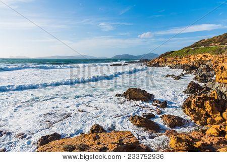 Waves In Alghero Rocky Shoreline. Sardinia, Italy