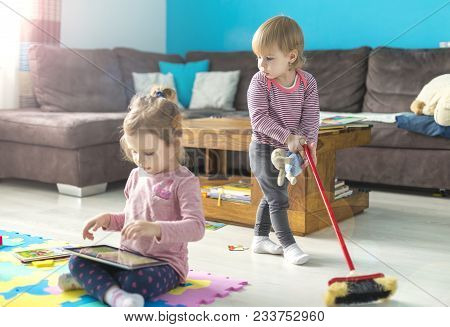 Cute Little Girl Is Using A Digital Tablet  Sitting On The Floor At Home In The Middle Of Toys. Her