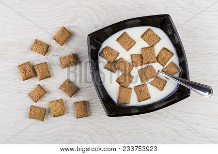 Black Bowl With Yogurt, Cereal Pillows, Spoon, Scattered Pillows On Wooden Table. Top View