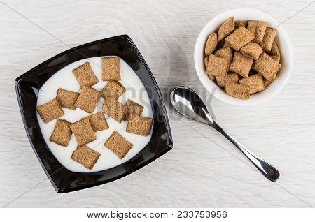 Black Bowl With Yogurt And Cereal Pillows, Bowl With Pillows, Spoon On Wooden Table. Top View