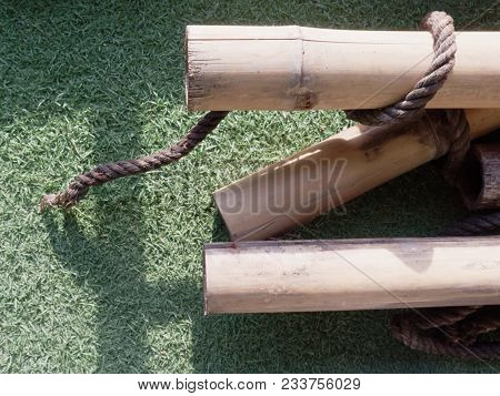 Pile Of Dry Brown Bamboo Sticks With Wooden Texture In Diagonal Over Green Astroturf On Background