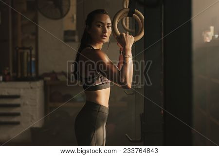 Fit Woman Holding Gymnast Rings At The Gym. Young Female Exercising At Gym.