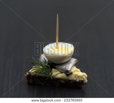 Mini Sandwich With Salt Sprat And Sliced Boiled Quail Egg On The Slice Of Bread. Canned Fish Is Esto