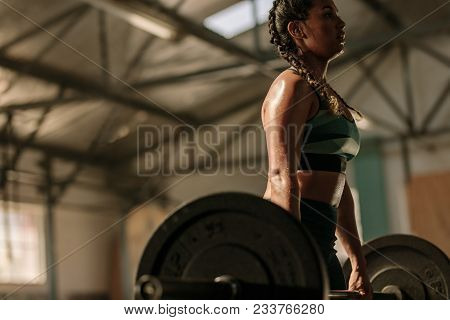 Muscular Woman In Gym Doing Heavy Weight Exercises. Young Woman Doing Weight Lifting At Health Club.
