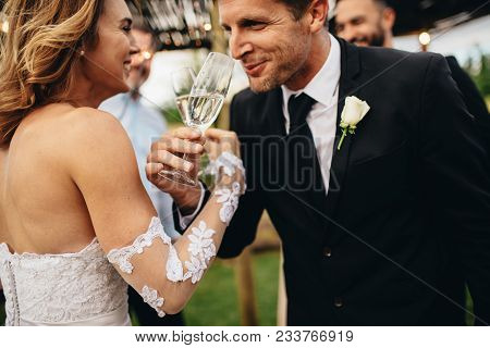 Newlyweds Clinking Glasses And Enjoying Romantic Moment Together At Wedding Reception Outside. Bride