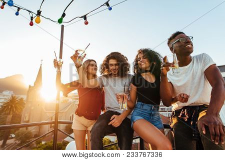 Group Of Young Friends Having Fun, Drinking And Enjoying A Evening On Rooftop. Multiracial Men And W