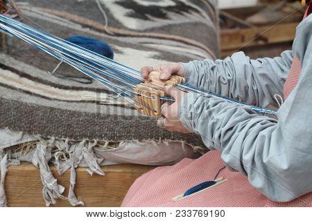 Female Hands Weaving A Traditional Ethnic Belt. Weaving On Planks