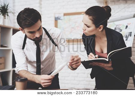 Private Detective Agency. Man With Holster Is Looking At Clue, Woman Is Taking Notes In Notebook.