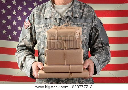 Closeup of a soldier wearing camouflage fatigues holding a stack of packages for mail call. Horizontal format, man is unrecognizable standing in front of an American Flag.