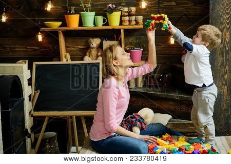 Nursery With Chalkboard On Background. Mother And Son Play With Constructor. Motherhood Concept. Fam