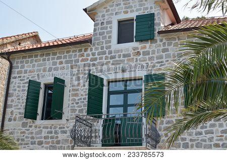 Coastal Villa Facade With Green Open Wooden Jalousies In Summertime
