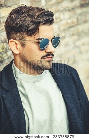 Cool Handsome Young Man With Modern Hairstyle. Fashion And Stylish Man With Sunglasses. A Charming A