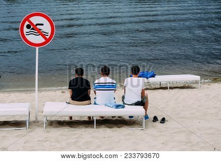 Three Men Are Sitting On The Beach And Watching The Sea Near The Sign Swimming Is Forbidden
