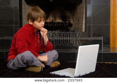 Boy At Fireplace On Computer.