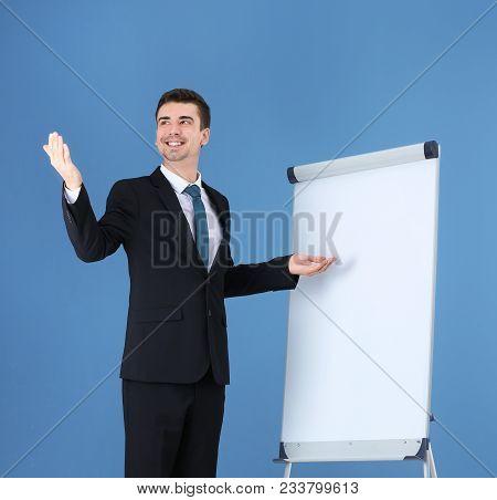 Business Trainer Giving Presentation On Flip Chart Board Against Color Background