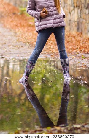 The Girl In Color Boots Jumping In Puddles After Rain