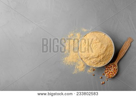 Bowl With Corn Flour And Kernels In Spoon On Gray Background