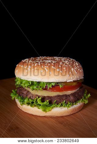Burger On Wooden Surface Isolated Black Background With Copyspace On Top. Hamburger Includes Salad,