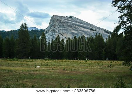 Big Granite Monolith In Yosemite National Park California With A Grassland In The Foreground. Cloudy
