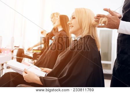 Female Stylist Combs Blond Straight Hair Of Mature Woman In Beauty Salon. Mature Pretty Woman Is Doi