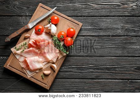 Board With Raw Bacon Rashers, Tomatoes And Garlic On Wooden Background