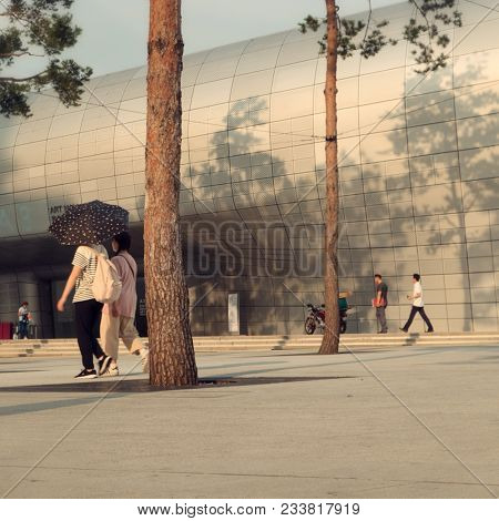 Seoul - July 2017: People walking in in front of Dongdaemun Design Plaza in evening light.