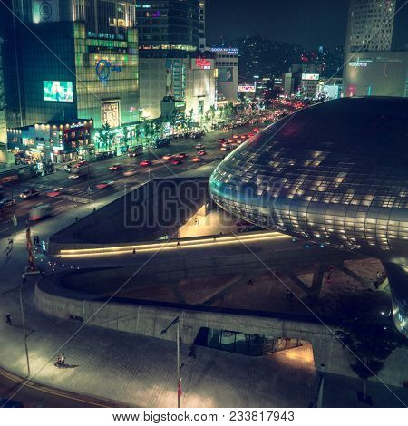 Seoul - July 2017: Elevated city view with traffic and Dongdaemun Design Plaza glowing at night.