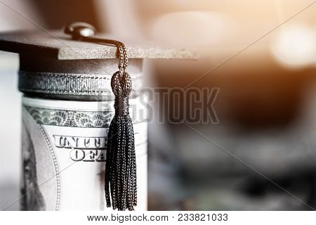 Concept Of International Graduate Study, Graduation Black Cap On Pile Of Foreign Money Us Dollars Mo