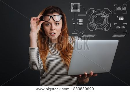 Good Statistics. Smart Enthusiastic Responsible Employee Holding A Convenient Laptop And Putting Her