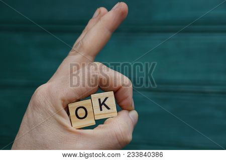 Hand Gesture And Wooden Letters With The Word Ok On A Green Background