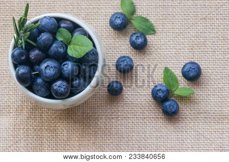 Fresh Ripe Wild Blueberries In White Bowl On Rustic Sack. Wild Blueberry In Top View Flat Lay With C