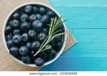 Fresh Ripe Wild Blueberries In White Bowl On Blue Wood Table. Fresh Blueberry In Top View Flat Lay W