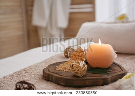 Burning Candle And Sea Salt On Massage Table In Spa Salon, Closeup
