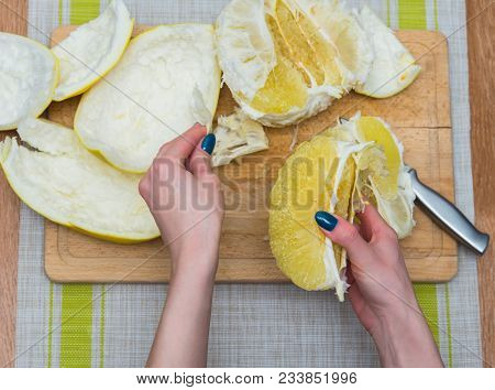 Girl Cleaning Her Hands With Pomelo, Citrus On A Wooden Board